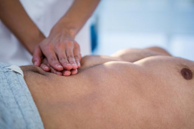 Fisioterapeuta dando massagem no estômago para um homem
