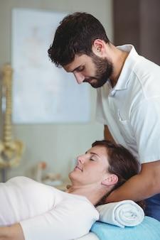 Fisioterapeuta dando massagem no pescoço para uma mulher