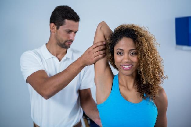 Fisioterapeuta dando massagem nos braços para paciente do sexo feminino