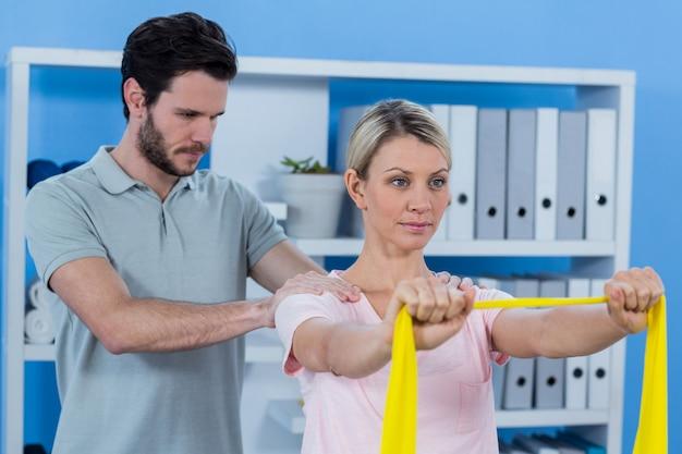 Fisioterapeuta dando massagem nos ombros para paciente