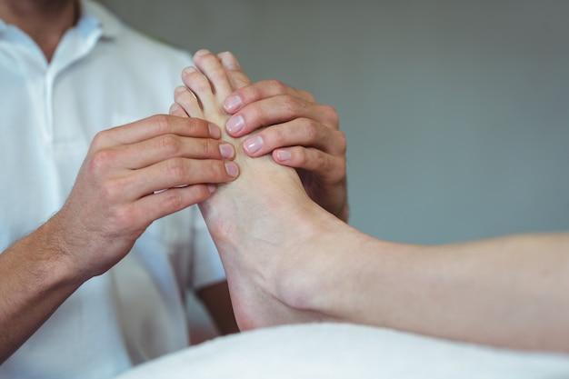 Fisioterapeuta dando massagem nos pés para uma mulher