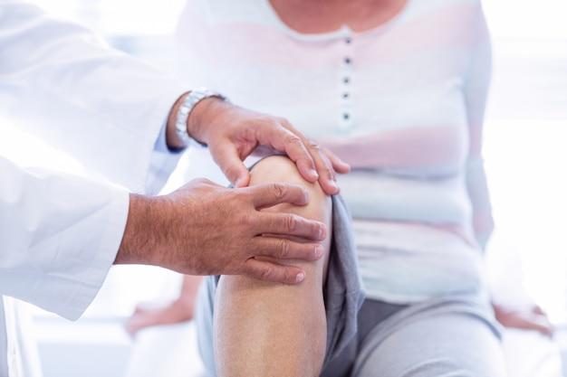 Fisioterapeuta dando terapia de joelho para mulher sênior