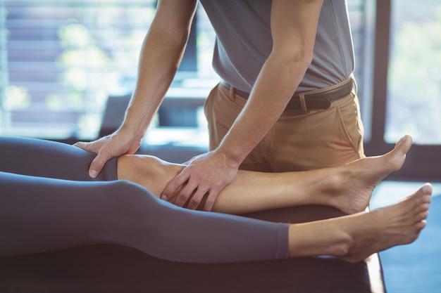 Fisioterapeuta dando terapia de joelho para uma mulher