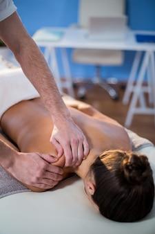 Fisioterapeuta dando terapia de ombro para uma mulher