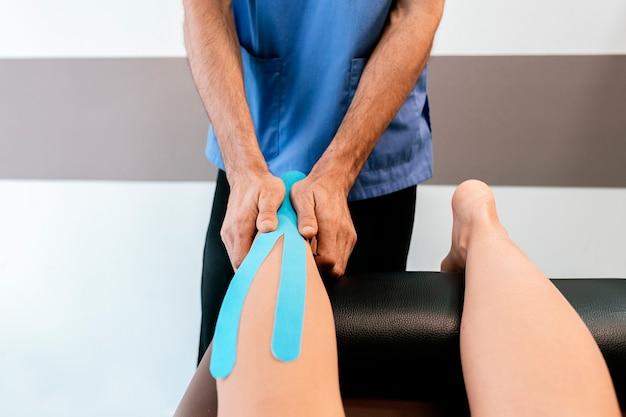 Fisioterapeuta dando terapia de panturrilha a uma mulher na clínica. conceito de tratamento físico