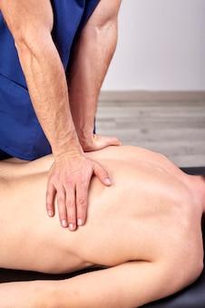 Fisioterapeuta dando uma massagem nas costas.