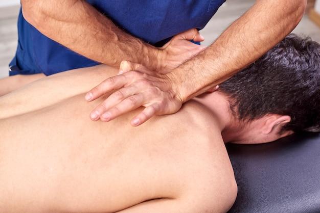 Fisioterapeuta dando uma massagem nas costas