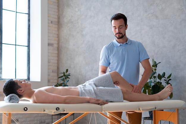 Fisioterapeuta de tiro médio verificando perna