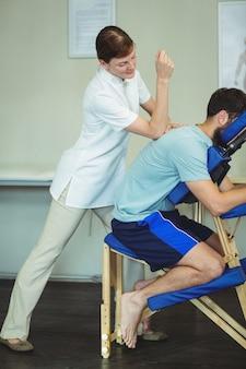 Fisioterapeuta, devolvendo a massagem para um paciente