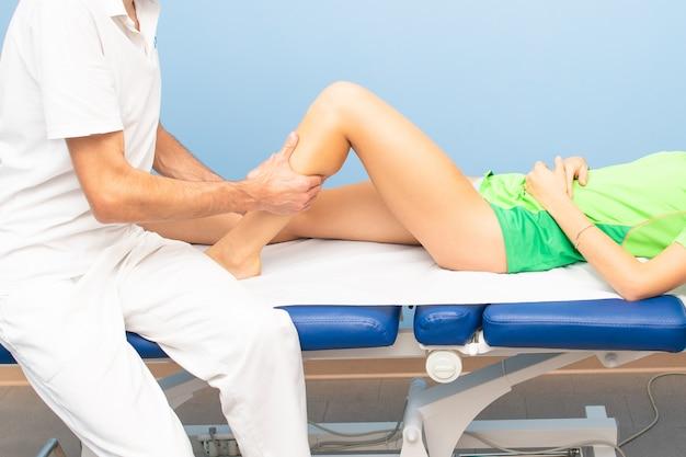 Fisioterapeuta durante uma massagem na panturrilha de um atleta