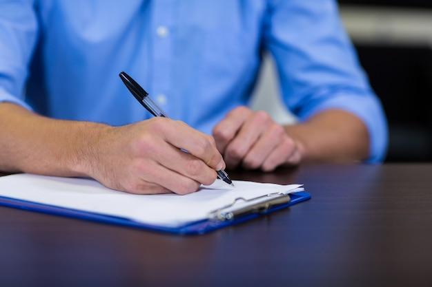 Fisioterapeuta, escrevendo sobre uma prancheta