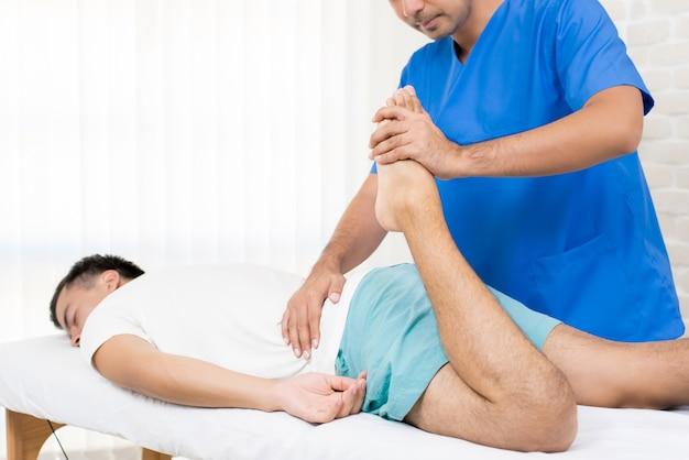 Fisioterapeuta, esticando a perna do paciente do sexo masculino na cama
