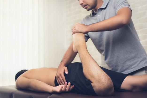 Fisioterapeuta, esticando a perna do paciente esportista