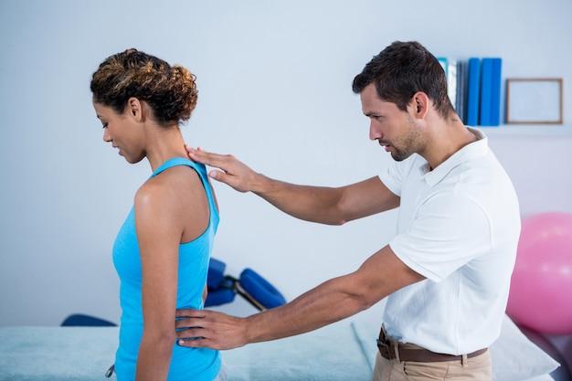 Fisioterapeuta examinando as costas da mulher