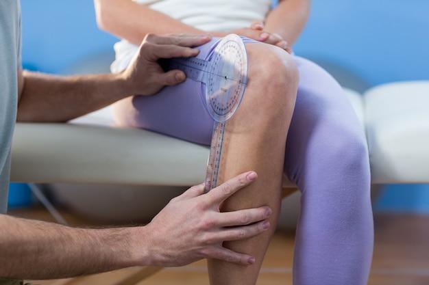 Fisioterapeuta examinando pacientes do joelho com goniômetro