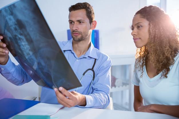 Fisioterapeuta, explicando o raio-x para o paciente