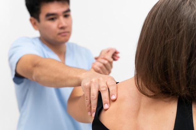 Fisioterapeuta fazendo exercícios para os ombros com paciente do sexo feminino