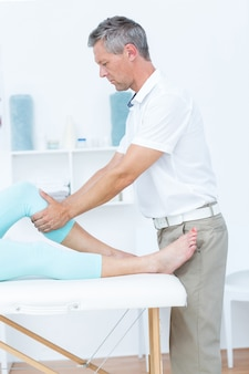 Fisioterapeuta fazendo massagem de perna para seu paciente