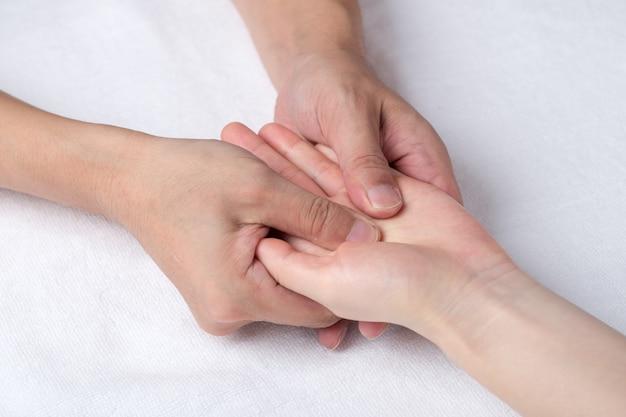 Fisioterapeuta fazendo massagem na mão no consultório médico