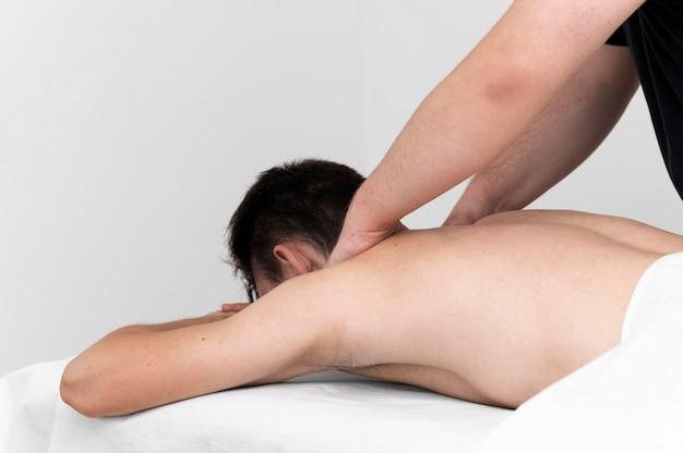 Fisioterapeuta fazendo massagem nas costas para homem