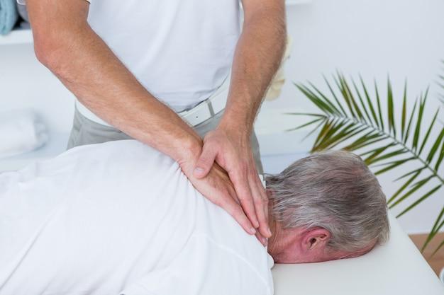 Fisioterapeuta fazendo massagem no pescoço para seu paciente