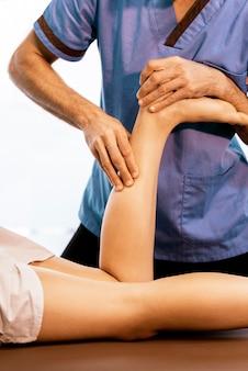 Fisioterapeuta fazendo terapia no joelho para uma mulher na clínica. conceito de tratamento físico