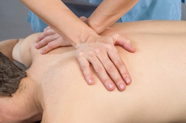 Fisioterapeuta fazendo uma massagem nas costas para homem paciente. osteopatia.