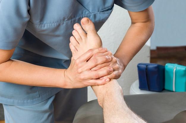 Fisioterapeuta fazendo uma massagem nos pés