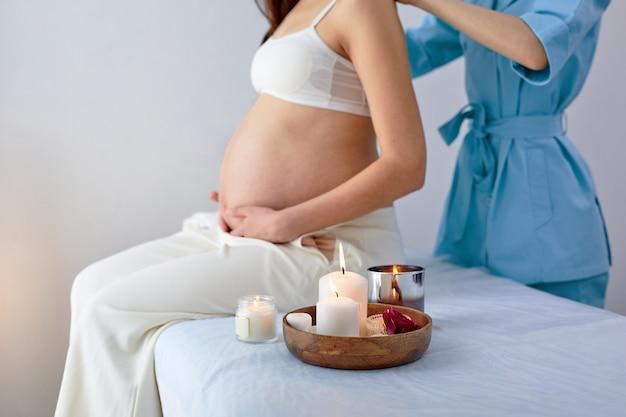 Fisioterapeuta feminina recortada massageando as costas e os ombros da mulher grávida, sentada na cama no armário do spa brilhante, com velas. a futura mamãe adulta está gostando de receber massagem