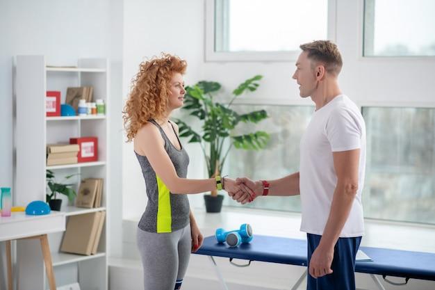 Fisioterapeuta masculina e paciente do sexo feminino apertando as mãos