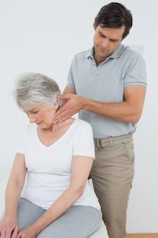 Fisioterapeuta masculina massageando o pescoço de uma mulher sênior