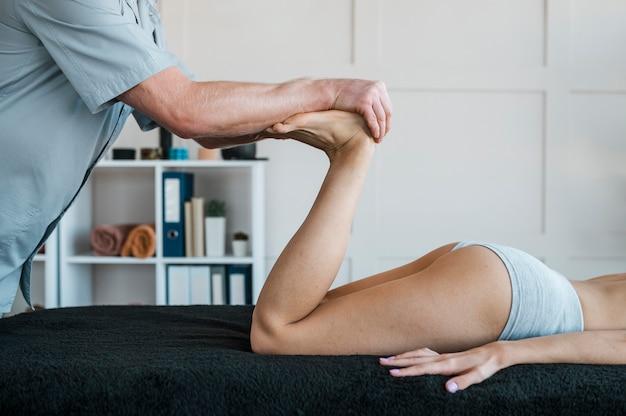 Fisioterapeuta masculino com mulher durante uma sessão de fisioterapia