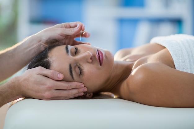 Fisioterapeuta masculino dando massagem na cabeça para paciente do sexo feminino