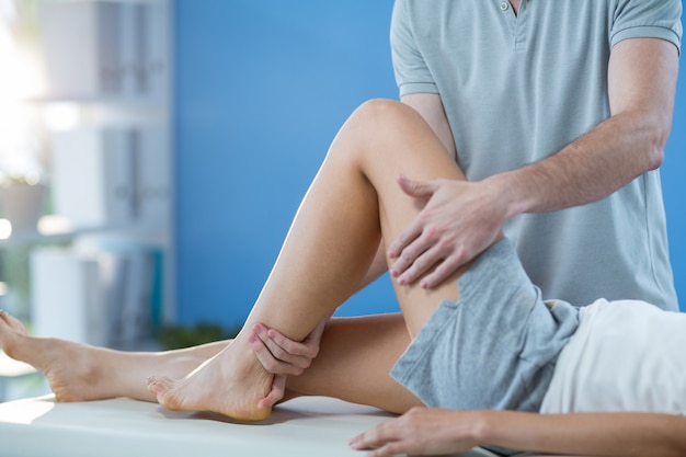 Fisioterapeuta masculino dando massagem no joelho para paciente do sexo feminino