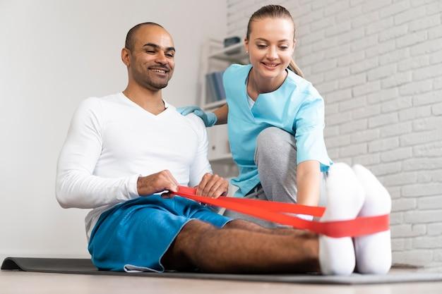 Fisioterapeuta masculino e feminino fazendo exercícios com elástico
