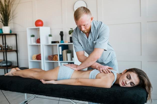 Fisioterapeuta masculino e mulher durante uma sessão de fisioterapia