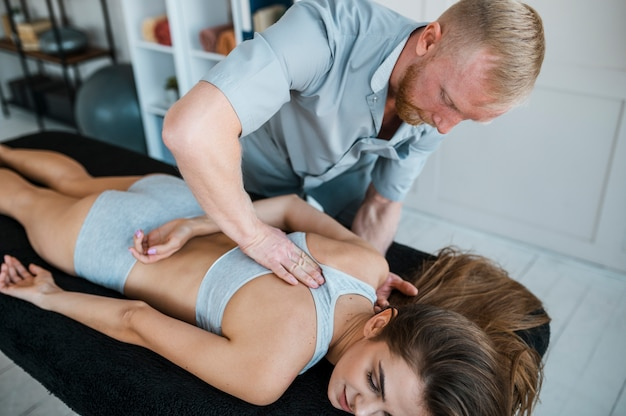 Fisioterapeuta masculino e paciente feminino durante sessão de fisioterapia