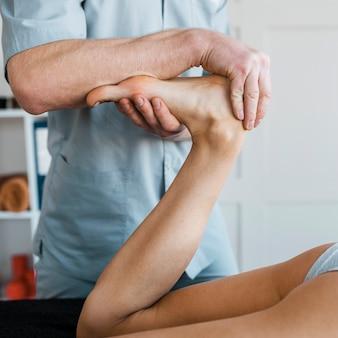 Fisioterapeuta masculino e paciente feminino durante uma sessão de massagem