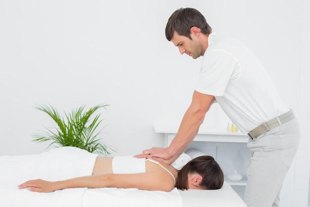 Fisioterapeuta masculino massageando mulher de volta