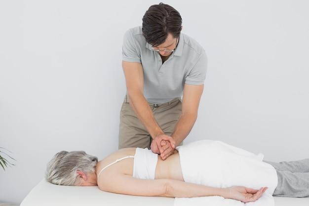 Fisioterapeuta masculino massageando uma mulher sênior de volta