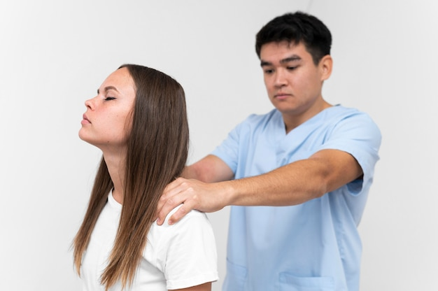 Fisioterapeuta massageando os ombros de pacientes do sexo feminino