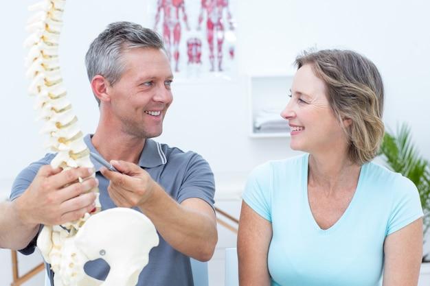 Fisioterapeuta mostrando modelo de coluna para o paciente