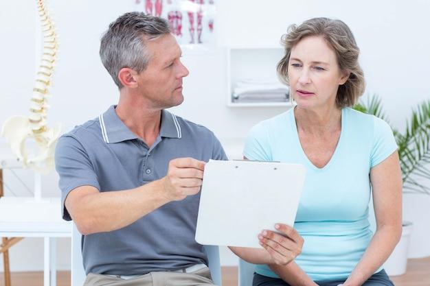Fisioterapeuta mostrando suas notas ao paciente