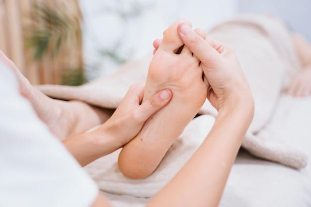 Fisioterapeuta mulher dando uma massagem nos pés para paciente do sexo feminino na clínica