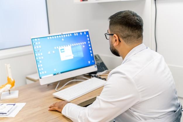 Fisioterapeuta no trabalho. o médico está sentado perto do computador. vista de trás.