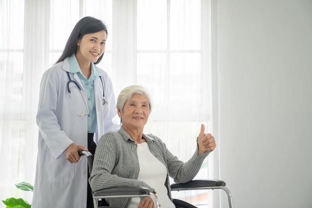 Fisioterapeuta, olhando para o paciente sênior, sentado na cadeira de rodas, médico e paciente na cadeira de rodas