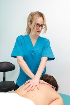 Fisioterapeuta profissional que cura um paciente ferido