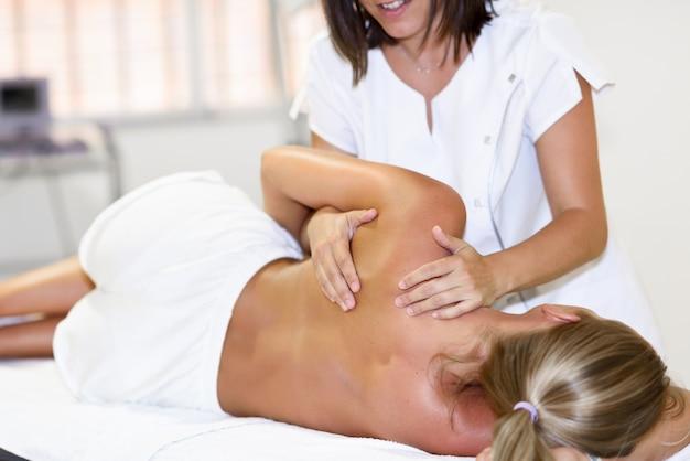 Fisioterapeuta profissional que dá massagem no ombro à mulher loira