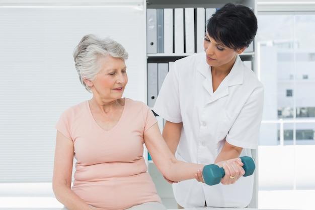 Fisioterapeuta que ajuda mulher sênior a levantar dumbbell