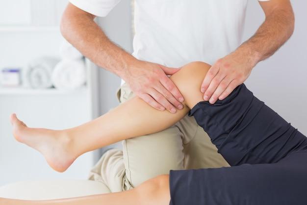 Fisioterapeuta que controla o joelho de um paciente